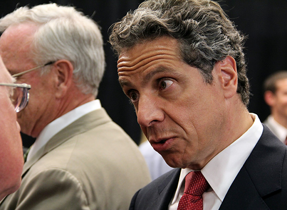 New York Governor Andrew Cuomo is seen in a closely-cropped photograph as he speaks to another man. Gov. Cuomo is wearing a blue suit with a red tie and has his head tilted down as he looks up intently in mid-speech.